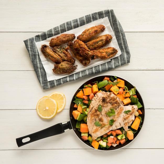 Asas de frango frito e filé com legumes Foto gratuita