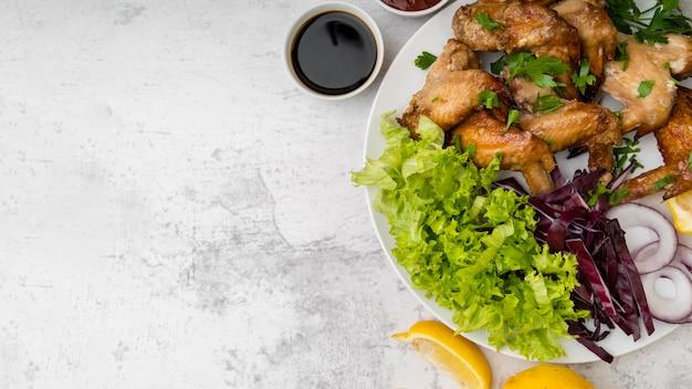 Asas de frango gostoso com salada e copie o espaço Foto gratuita