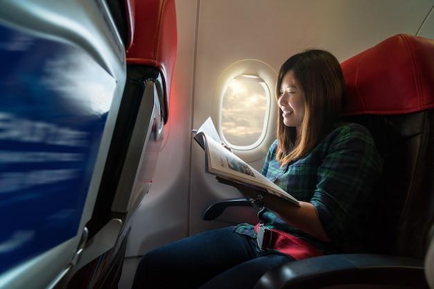 Ásia jovem mulher lendo a revista enquanto viaja dentro do avião ao lado do windo Foto Premium