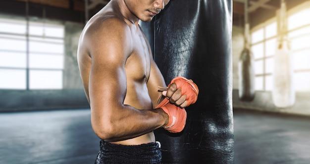 Ásia muay thai com ataduras de boxe com luva de boxe, preparando-se para o treinamento de lutador. Foto Premium