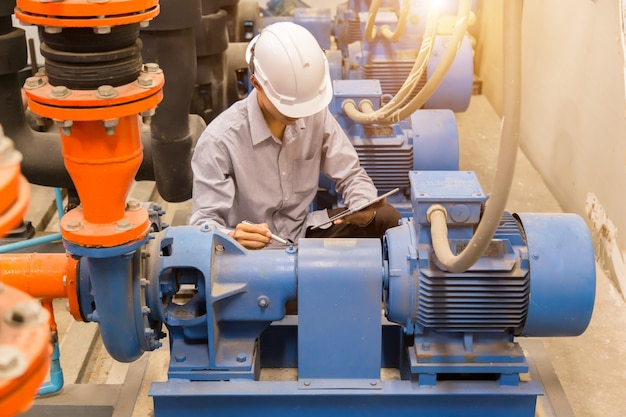 Asian engineer checking condenser bomba de água Foto Premium