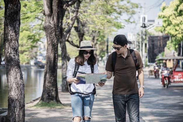 Asiancouple turista segurando o mapa da cidade atravessando a estrada Foto gratuita