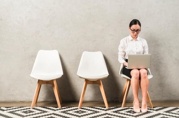 Asiática jovem empresária séria sentado na cadeira, digitando sobre o laptop Foto gratuita