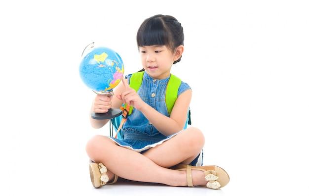 Asiática linda garota olhando para o globo Foto Premium