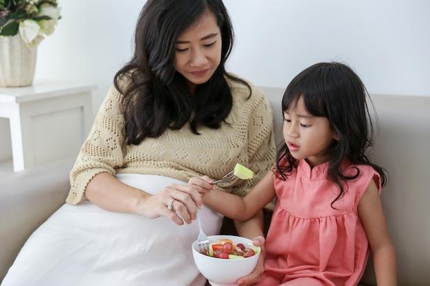 Asiática mãe e filha juntos a comer salada Foto Premium