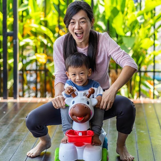 Asiática mãe solteira com filho estão brincando com o brinquedo do carro juntos quando vivendo em casa moderna Foto Premium