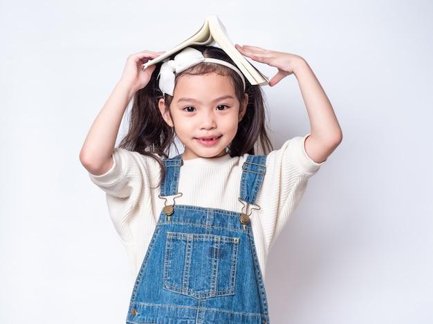 Asiática menina bonitinha colocar o livro na cabeça e olhando. vista lateral da criança adorável pré-escolar com o livro isolado Foto Premium