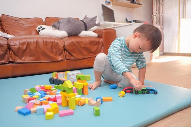 Asiático 2 - 3 anos de idade menino criança se divertindo brincando com brinquedos de madeira do bloco de construção indoor em casa Foto Premium