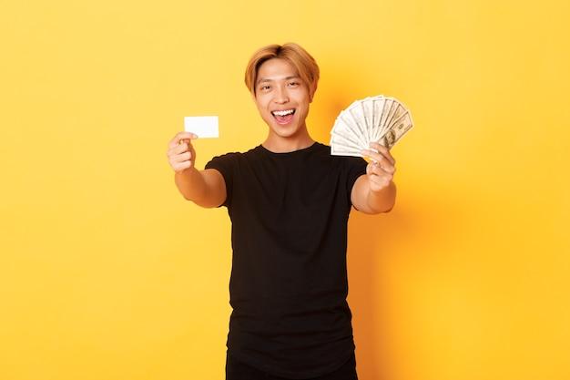 Asiático bonito e feliz em roupas pretas casuais, mostrando dinheiro e cartão de crédito, sorrindo atrevido, parede amarela Foto gratuita