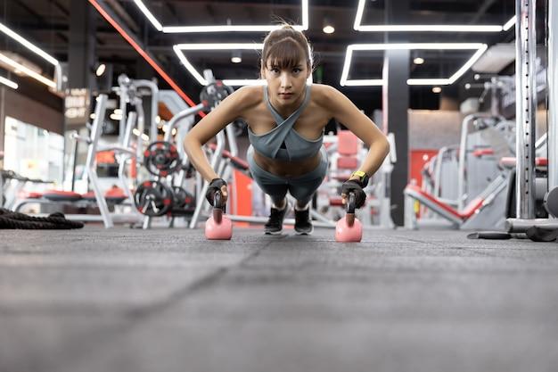 Asiático bonito novo da mulher que faz exercícios com kettlebell. push-up em pesos no ginásio. Foto Premium