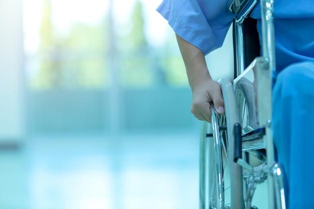 Asiático com deficiência homem está sentado em uma cadeira de rodas. ele segura as mãos no volante, medical eq Foto Premium