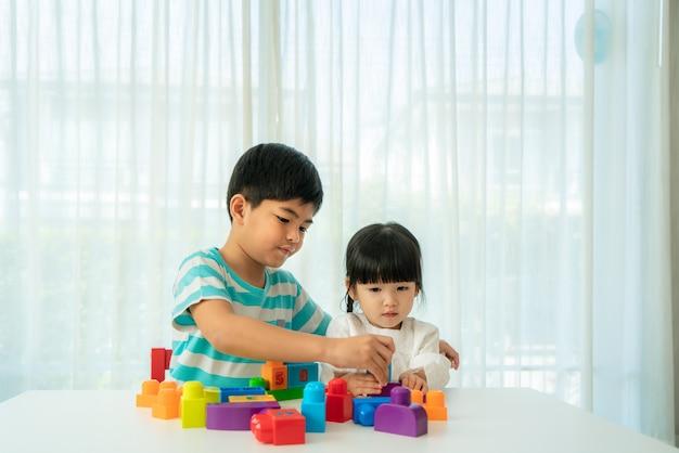 Asiático fofo irmão e irmã brincando com brinquedos Foto Premium