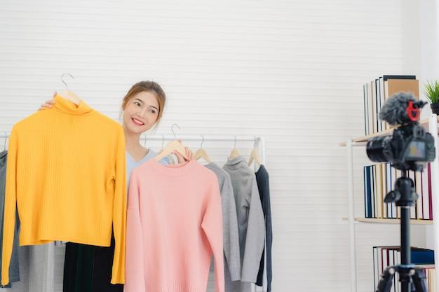 Asiático moda feminina blogger on-line influenciador segurando sacolas de compras e muitas roupas Foto gratuita