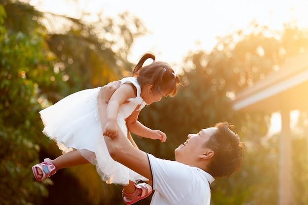 Asiático pai carregando a filha no ar e tocando juntos no parque Foto Premium