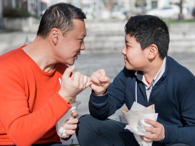 Asiático pai e filho mindinho promessa Foto gratuita