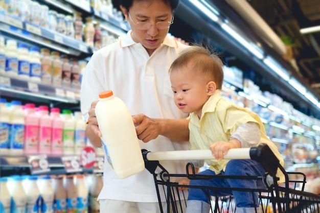 Asiático pai & menino criança escolhendo produtos lácteos na mercearia Foto Premium