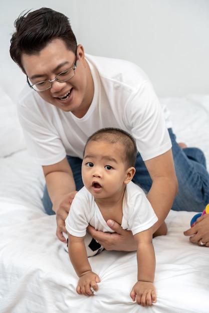 Asiático pai tocando e brincando com o bebê menino na cama na casa Foto Premium