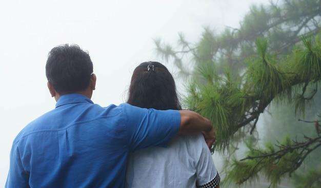 Asiático, par velho, abraçando, com, árvore pinho Foto Premium