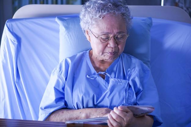 Asiático, sênior, ou, idoso, senhora velha, mulher, paciente, lendo um livro, enquanto, sentar-se cama, em, hosp Foto Premium