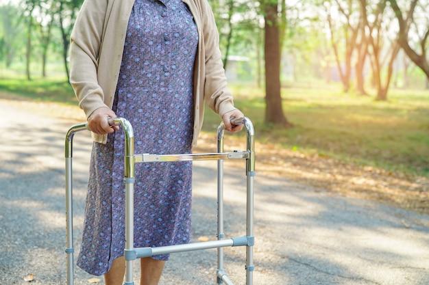 Asiático, sênior, ou, idoso, senhora velha, mulher, paciente, passeio, com, caminhante, em, parque Foto Premium