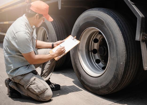 Asiático, um motorista de caminhão segurando uma prancheta está verificando a segurança das rodas e pneus de um caminhão. Foto Premium