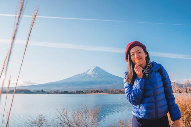 Asiáticos linda mulher sorridente turistas estão viajando e se sentir feliz no campo de grama seca Foto Premium