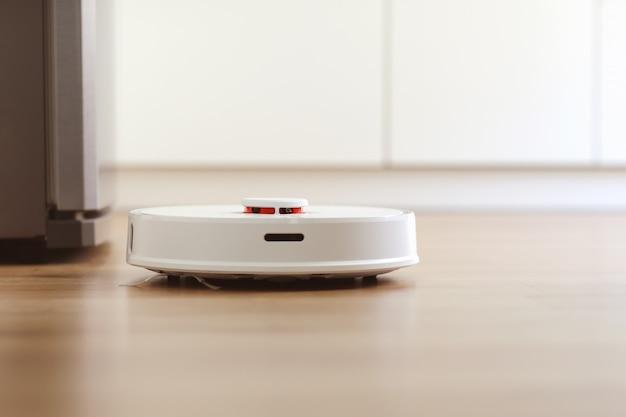 Aspirador robô branco limpa o chão Foto Premium