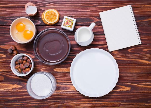 Assadeira branca; gema de ovo; granulados; avelãs; leite; farinha; xarope de chocolate e bloco de notas em espiral no plano de fundo texturizado de madeira Foto gratuita