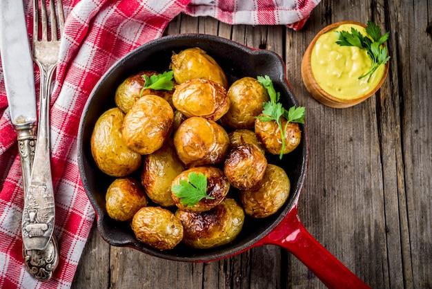 Assado na frigideira, batatas jovens inteiras, comida vegetariana caseira, mesa rústica velha de madeira, com molho, cópia espaço Foto Premium