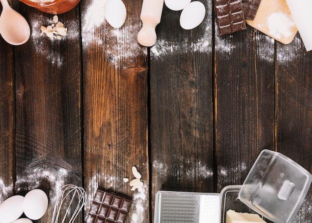 Assar um bolo ingredientes com utensílio de cozinha no tampo da mesa de madeira Foto gratuita