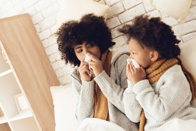 Assento sneazing africano doente da mãe e da filha na cama. Foto Premium