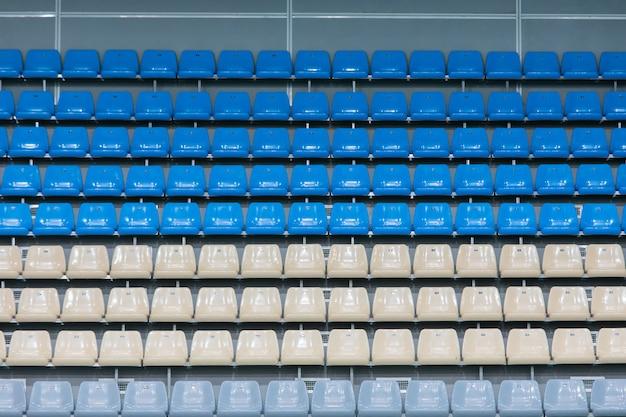 Assentos de plástico coloridos vazios na plataforma de visualização do complexo de piscinas cobertas antes da competição Foto Premium