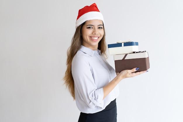 Assistente de escritório de natal sorridente levando presentes Foto gratuita
