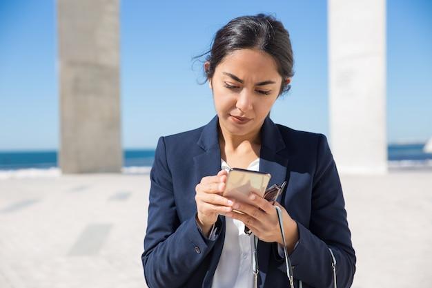 Assistente de escritório focada lendo na tela do telefone Foto gratuita