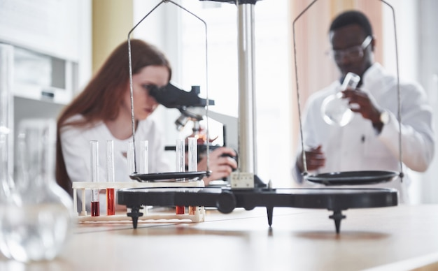 Assistente de laboratório com lâmpada de vidro de laboratório de microscópio com produtos químicos. Foto gratuita