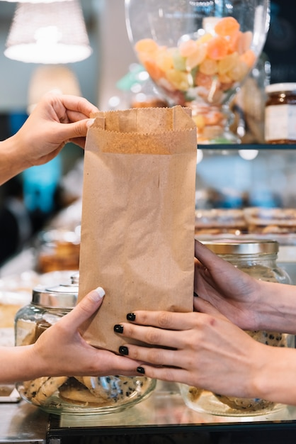Assistente de loja dando croissant bag Foto gratuita