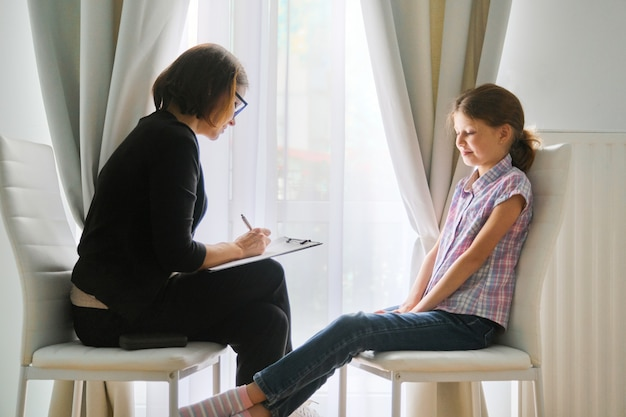Assistente social de mulher falando com a garota. psicologia infantil, saúde mental Foto Premium