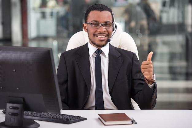 Assistente sorridente está usando um fone de ouvido em um call center. Foto Premium