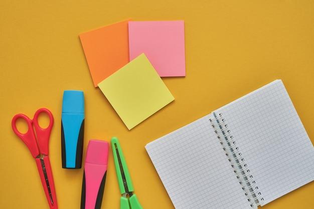 Assuntos escolares em um fundo amarelo. volta ao conceito de escola. lay plana, copie o espaço Foto Premium