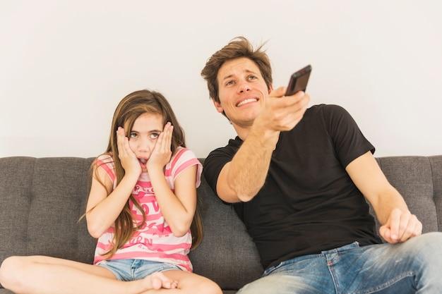 Assustado menina sentada com o pai dela segurando o controle remoto Foto gratuita