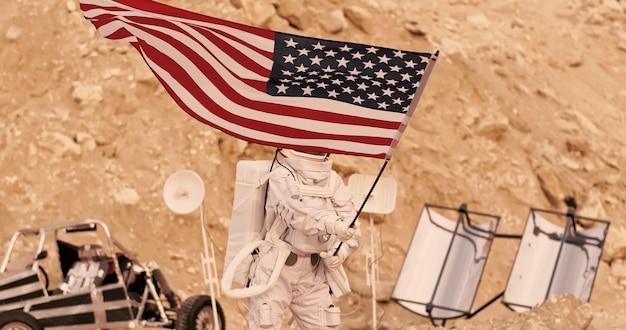Astronauta com a bandeira americana em pé nas montanhas rochosas do planeta vermelho alienígena / marte. primeira missão tripulada em marte Foto Premium