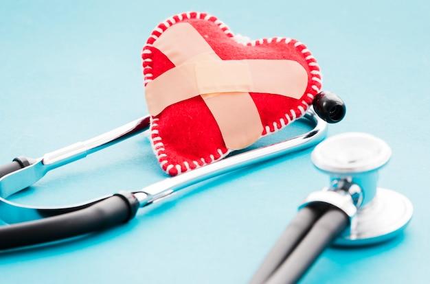 Atadura cruzada sobre o coração de tecido macio vermelho e estetoscópio no fundo azul Foto gratuita
