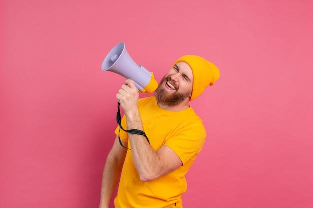 Atenção! homem europeu gritando no megafone no fundo rosa Foto gratuita