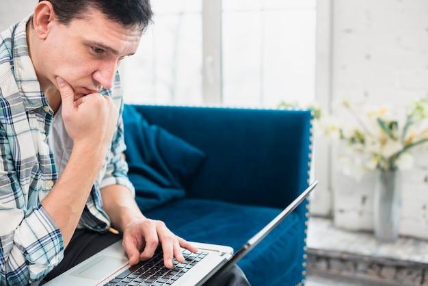 Atento homem olhando para laptop em casa Foto gratuita