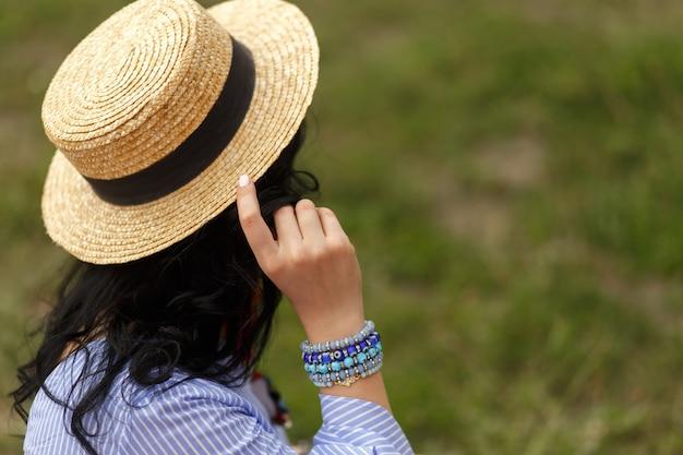 Atirar de costas de mulher segurar seu chapéu. Foto Premium