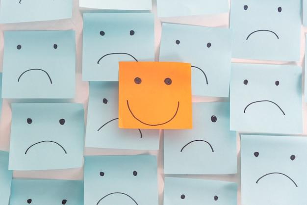 Atitude positiva e feliz conceito. mão desenhada um rosto de sorriso e emoção triste em não pegajosa Foto Premium