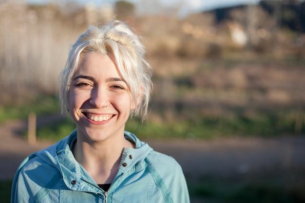 Ativa alegre loira parando depois de uma corrida em um parque em um dia ensolarado Foto Premium