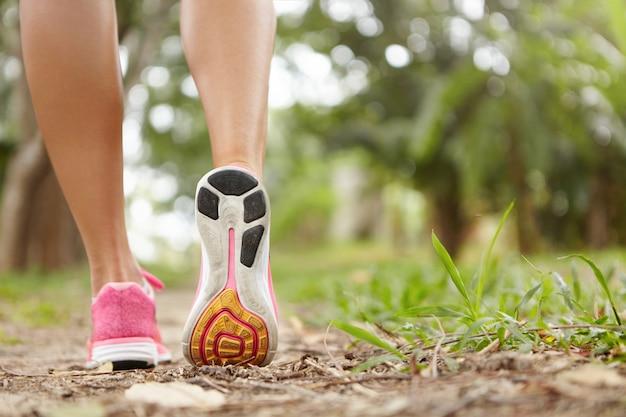 Atividades ao ar livre e esportes. congele o close up da ação de tênis rosa contra a grama verde. atleta de mulher se exercitando no parque ou na floresta, preparando-se para a maratona. Foto gratuita