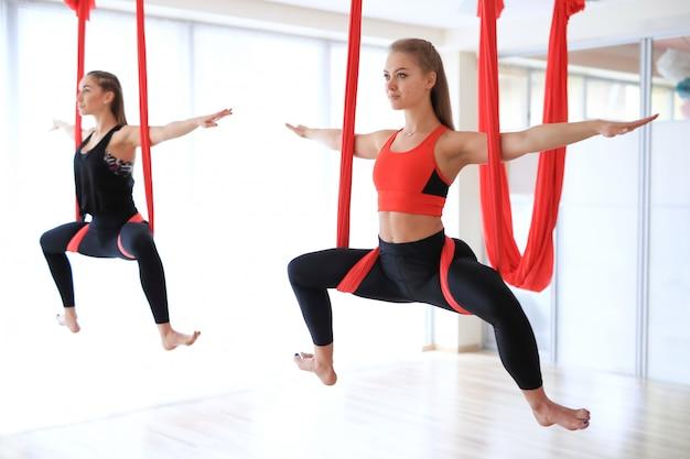 Atividades de yoga em grupo penduradas no linho vermelho Foto gratuita