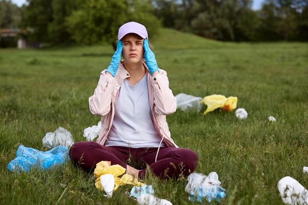 Ativista ambiental cansada, sentado na grama verde, com os dedos nos templos Foto gratuita